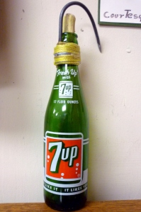 Coal oil, which is distilled from shale coal, was used to lubricate the saw blade. Just about any bottle would do as this 7-UP bottle shows. The hook was used to hang the bottle on a log.